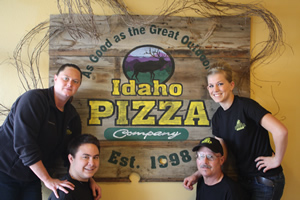 Idaho Pizza Company Employees surround a printed Idaho Pizza logo sign.